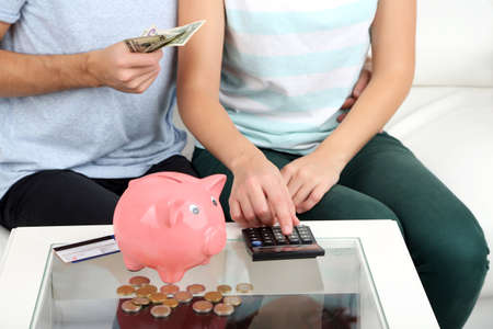 Loving couple sitting in sofa with piggy bank in room photo