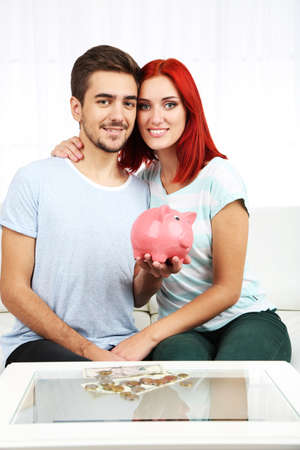 stash: Loving couple sitting in sofa with piggy bank in room Stock Photo