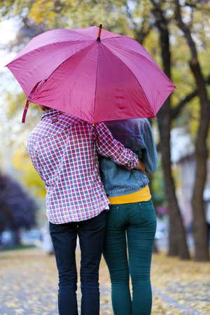 uomo sotto la pioggia: Amare coppia sotto un ombrello in autunno parco