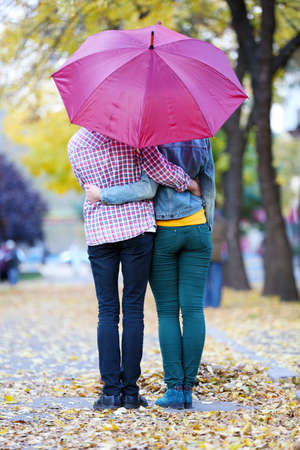 emotional couple: Loving couple under an umbrella in autumn park