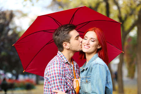 affectionate action: Loving couple kissing under an umbrella in autumn park