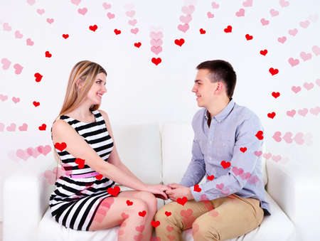 Loving couple sitting on sofa and heart-shaped frame, on light background photo