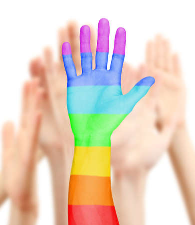 Mans hand painted as the rainbow flag on other hands background photo