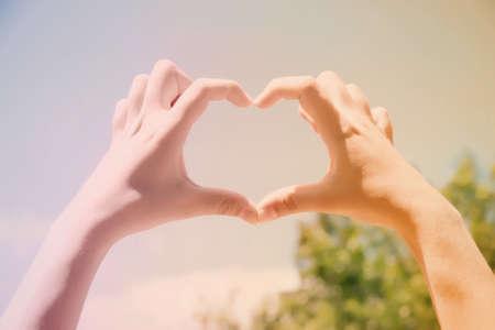 simbolo della pace: Giovane donna che tiene le mani a forma di cuore cornice su sfondo blu cielo