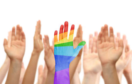 Mans hand painted as the rainbow flag on other hands background isolated on white photo