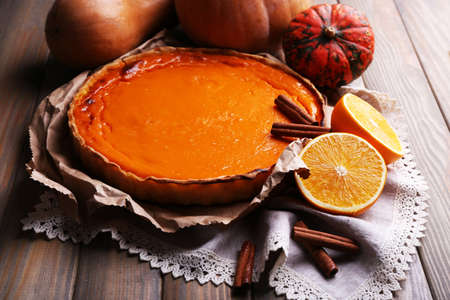 Homemade pumpkin pie on napkin, on wooden background photo