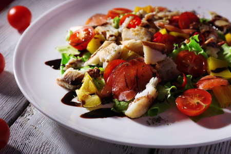 Appetizing fish salad with vegetables on plate close-up