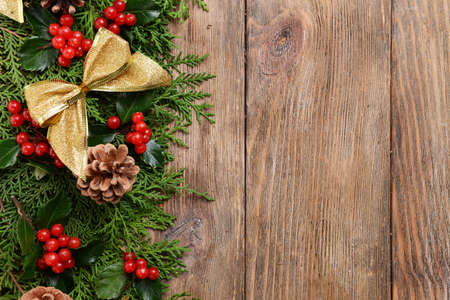 christmas beads: Beautiful Christmas border from fir and mistletoe on wooden background