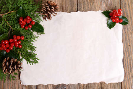 christmas holly: Christmas decoration with paper sheet on wooden background