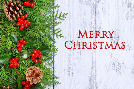 Beautiful Christmas border from fir and mistletoe on wooden background photo