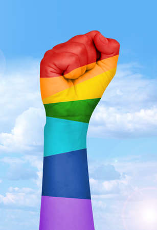 homosexual partners: Mans hand painted as the rainbow flag isolated on white