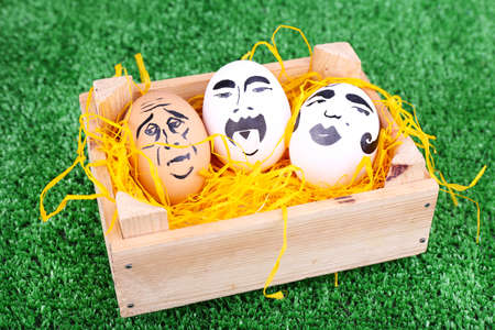 Eggs in wooden box on green background photo