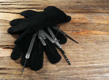 picks: Lock picks with gloves on wooden table