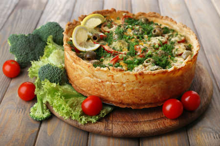 Vegetable pie with broccoli, peas, tomatoes and cheese on wooden background photo