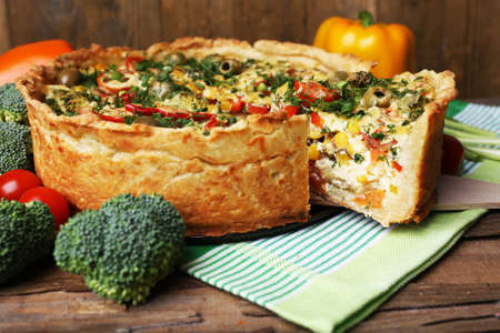 Vegetable pie with broccoli, peas, tomatoes and cheese on napkin, on wooden background photo