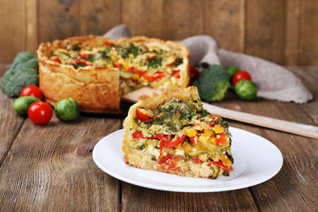 Piece of Vegetable pie with broccoli, peas, tomatoes and cheese on plate, on wooden background photo
