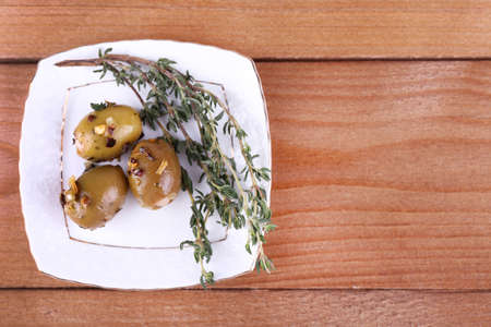 Green olives in oil with spices and rosemary on plate on wooden table photo