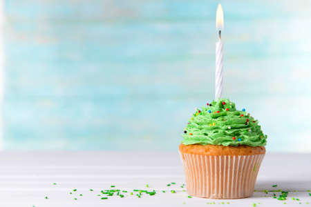 Delicious birthday cupcake on table on light blue background photo