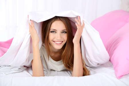 awaking: Young beautiful woman lying in bed Stock Photo