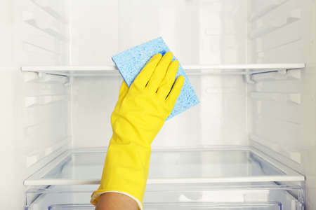 duster: Womans hand washing refrigerator with duster Stock Photo