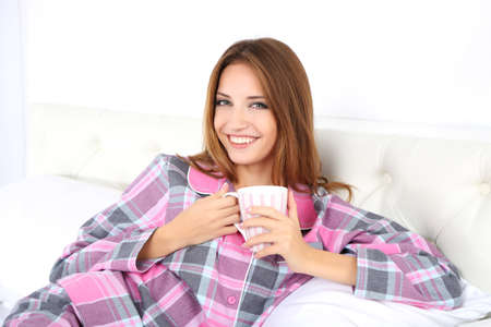 awaking: Young beautiful woman lying in bed with cup of hot drink
