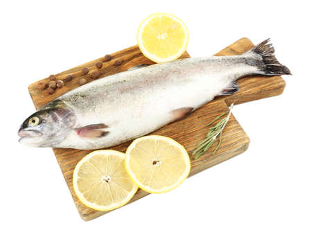 Fresh raw fish on cutting board and food ingredients isolated on white photo