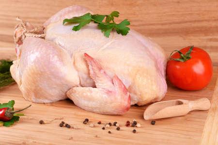 carne de pollo: Pollo crudo en mesa de madera