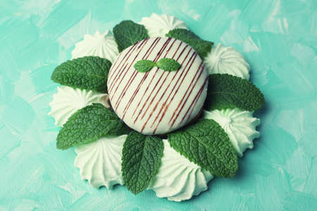 kiss biscuits: Mint color meringues and tasty cake on color background