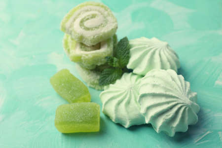 kiss biscuits: Mint color meringues and candies on color background