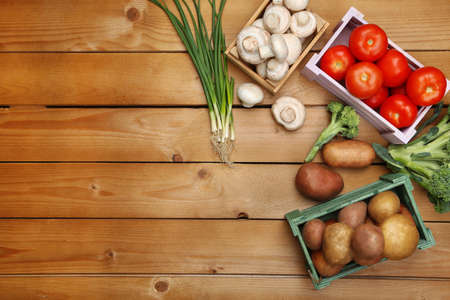 Different vegetables in boxes on wooden background top view photo