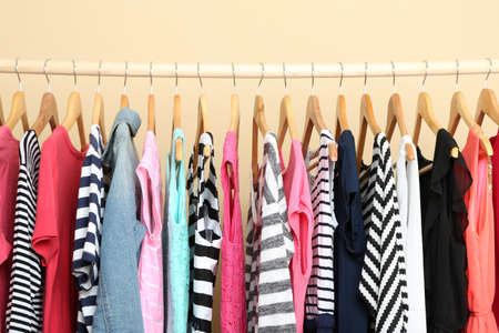 ropa colgada: Ropa de colores en perchas en la habitación