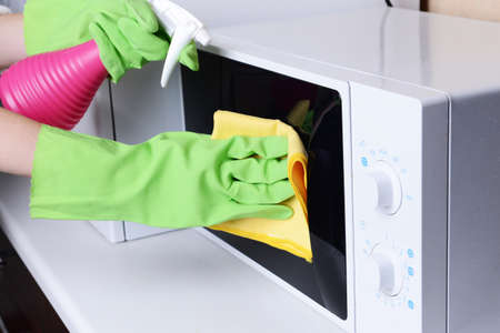 Cleaning microwave oven in kitchen close-up Imagens - 34949757