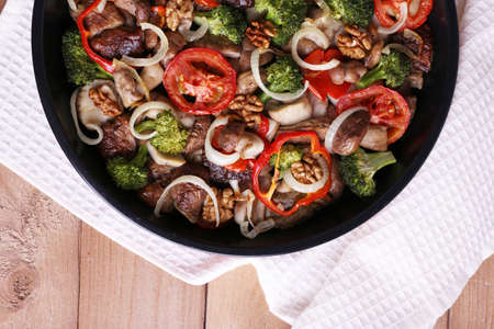 braised mushrooms: Braised wild mushrooms with vegetables and spices in pan close-up