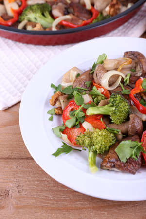 braised mushrooms: Braised wild mushrooms with vegetables and spices in pan and plate on table