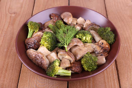 braised mushrooms: Braised wild mushrooms with vegetables and spices in plate on table