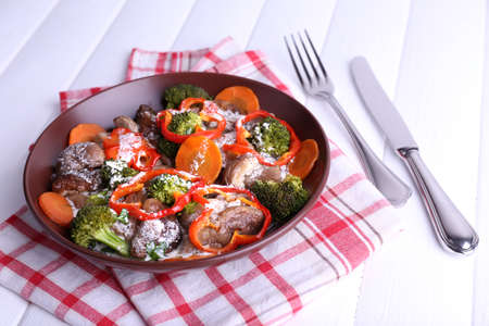 braised mushrooms: Braised wild mushrooms with vegetables and sauce in plate on table Stock Photo