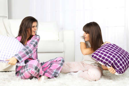 room mate: Beautiful girls twins in pajamas fight pillows at home