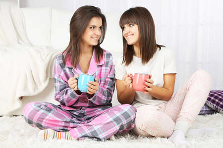 drinking tea: Beautiful girls twins in pajamas drinking tea at home Stock Photo
