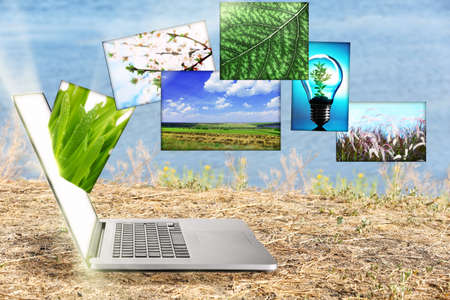 Laptop and eco theme images on nature background photo