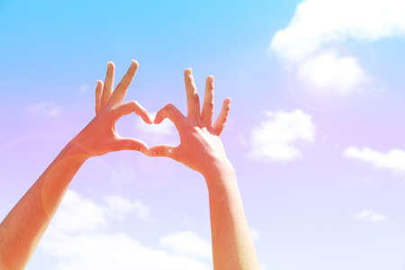 girl holding sign: Young womans hands making heart shape frame on blue sky  Stock Photo