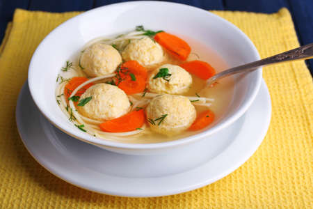 Soup with meatballs and noodles in bowl on wooden background photo
