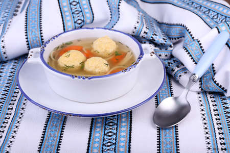 Soup with meatballs and noodles in bowl, on napkin, on wooden background photo