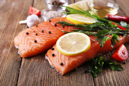 Fresh salmon with spices and lemon on wooden table Archivio Fotografico
