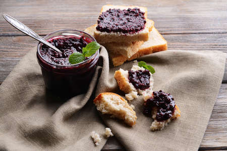 Delicious black currant jam on table close-up photo
