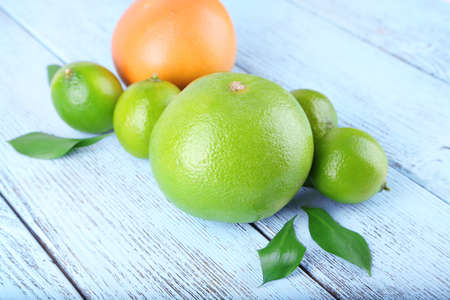 sweetie: Ripe grapefruits and limes on wooden background