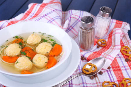 Soup with meatballs and noodles in bowl on wooden  photo