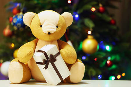 Teddy bear and gift box on Christmas tree background photo