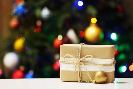 Gift box on Christmas tree lights background Reklamní fotografie