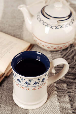 Cup of tea with book on table close-up photo