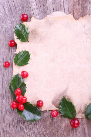 ilex aquifolium holly: Empty paper with European Holly (Ilex aquifolium) with berries on wooden background Stock Photo
